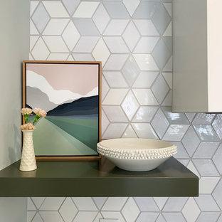 Inredning av ett 50 tals mellanstort vit vitt kök, med en nedsänkt diskho, släta luckor, gröna skåp, bänkskiva i onyx, grått stänkskydd, stänkskydd i keramik, rostfria vitvaror, ljust trägolv, en köksö och brunt golv