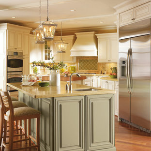 Inspiration for a traditional eat-in kitchen in Other with stainless steel appliances, raised-panel cabinets, green cabinets, with island, yellow splashback and brown benchtop.