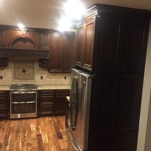 シーダーラピッズの中サイズのヴィクトリアン調のおしゃれなキッチン (アンダーカウンターシンク、落し込みパネル扉のキャビネット、濃色木目調キャビネット、珪岩カウンター、ベージュキッチンパネル、モザイクタイルのキッチンパネル、シルバーの調理設備の、濃色無垢フローリング、茶色い床) の写真