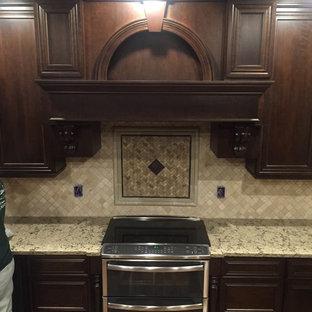 シーダーラピッズの中くらいのヴィクトリアン調のおしゃれなキッチン (アンダーカウンターシンク、落し込みパネル扉のキャビネット、濃色木目調キャビネット、珪岩カウンター、ベージュキッチンパネル、モザイクタイルのキッチンパネル、シルバーの調理設備、濃色無垢フローリング、茶色い床) の写真