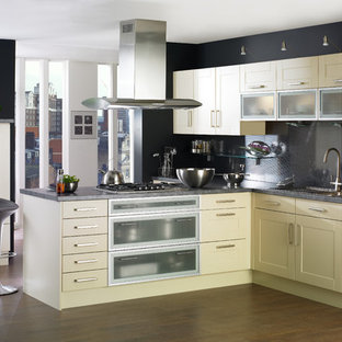 Inspiration for a contemporary l-shaped kitchen in London with shaker cabinets, granite worktops, stainless steel appliances, beige cabinets, black splashback and glass sheet splashback.