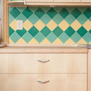 Kleine Retro Küche ohne Insel in U-Form mit Vorratsschrank, flächenbündigen Schrankfronten, hellen Holzschränken, Laminat-Arbeitsplatte, Küchenrückwand in Grün, Rückwand aus Keramikfliesen, Küchengeräten aus Edelstahl und Linoleum in Minneapolis