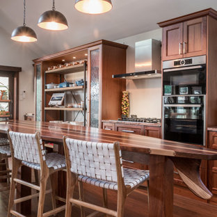 This is an example of a beach style galley kitchen in Other with recessed-panel cabinets, medium wood cabinets, stainless steel appliances, medium hardwood floors, with island, brown floor and brown benchtop.