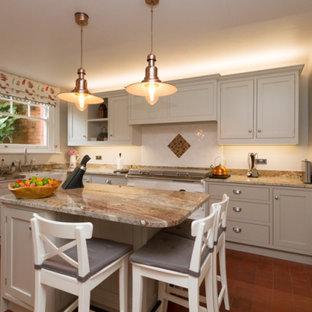 グロスタシャーの広いおしゃれなキッチン (ダブルシンク、シェーカースタイル扉のキャビネット、グレーのキャビネット、御影石カウンター、白いキッチンパネル、セラミックタイルのキッチンパネル、パネルと同色の調理設備、テラコッタタイルの床、赤い床、茶色いキッチンカウンター) の写真