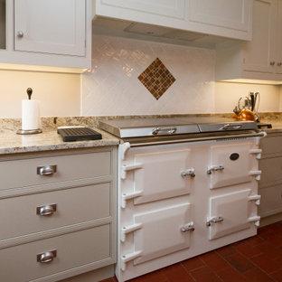 グロスタシャーの広いトラディショナルスタイルのおしゃれなキッチン (ダブルシンク、シェーカースタイル扉のキャビネット、グレーのキャビネット、御影石カウンター、白いキッチンパネル、セラミックタイルのキッチンパネル、シルバーの調理設備、テラコッタタイルの床、赤い床、緑のキッチンカウンター) の写真