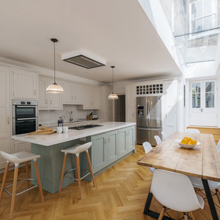 Medium sized traditional l-shaped kitchen/diner in London with light hardwood flooring, an island, beige floors, a submerged sink, shaker cabinets, blue cabinets, white splashback and stainless steel appliances.