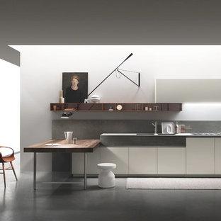 Foto på ett mellanstort funkis linjärt kök med öppen planlösning, med en halv köksö, en integrerad diskho, släta luckor, vita skåp, bänkskiva i betong, grått stänkskydd, integrerade vitvaror och betonggolv