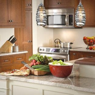 ニューヨークの小さいトロピカルスタイルのおしゃれなキッチン (レイズドパネル扉のキャビネット、中間色木目調キャビネット、御影石カウンター、白いキッチンパネル、シルバーの調理設備の) の写真