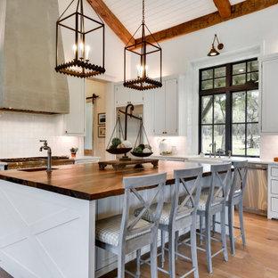 Inspiration för rustika vitt l-kök, med en rustik diskho, skåp i shakerstil, vita skåp, vitt stänkskydd, rostfria vitvaror, ljust trägolv, en köksö och beiget golv