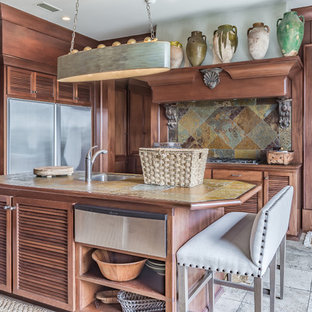 Photo of a large tropical kitchen in Miami with tile benchtops, stainless steel appliances, limestone floors, with island, a single-bowl sink, louvered cabinets, medium wood cabinets, multi-coloured splashback and slate splashback.