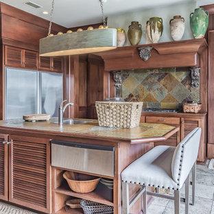 Exemple d'une grand cuisine exotique avec un plan de travail en carrelage, un électroménager en acier inoxydable, un sol en calcaire, un îlot central, un évier 1 bac, un placard à porte persienne, des portes de placard en bois brun, une crédence multicolore et une crédence en ardoise.