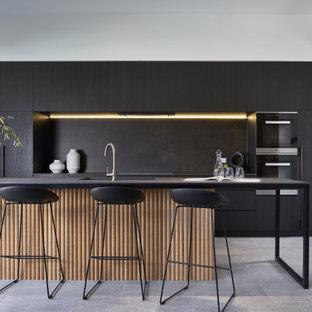 Modelo de cocina de galera, minimalista, con fregadero bajoencimera, armarios con paneles lisos, puertas de armario negras, salpicadero negro, electrodomésticos de acero inoxidable, una isla y suelo gris