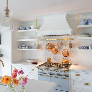 Diseño de cocina en L, tradicional renovada, abierta, con armarios con paneles empotrados, puertas de armario blancas, salpicadero blanco, salpicadero de azulejos tipo metro, electrodomésticos de colores, una isla y encimeras blancas