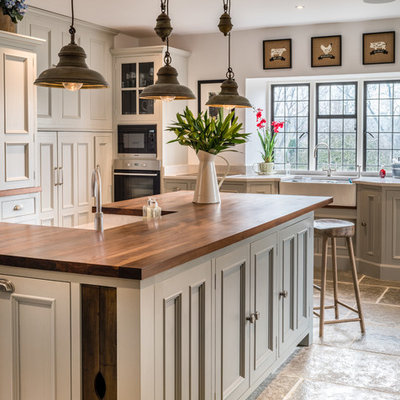 Example of a farmhouse kitchen design in Other with a farmhouse sink, beaded inset cabinets, gray cabinets, wood countertops, stainless steel appliances, an island and brown countertops