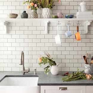 ニューヨークの小さいカントリー風おしゃれなキッチン (エプロンフロントシンク、シェーカースタイル扉のキャビネット、白いキャビネット、ソープストーンカウンター、白いキッチンパネル、サブウェイタイルのキッチンパネル、シルバーの調理設備の、無垢フローリング) の写真