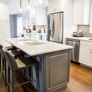 Mid-sized transitional eat-in kitchen inspiration - Eat-in kitchen - mid-sized transitional l-shaped medium tone wood floor and brown floor eat-in kitchen idea in Chicago with an undermount sink, raised-panel cabinets, white cabinets, quartz countertops, gray backsplash, ceramic backsplash, stainless steel appliances, an island and white countertops