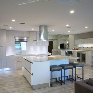 Photo of a mid-sized tropical eat-in kitchen in Miami with a single-bowl sink, flat-panel cabinets, light wood cabinets, quartz benchtops, stainless steel appliances, porcelain floors and with island.