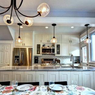 ワシントンD.C.の中サイズのエクレクティックスタイルのおしゃれなキッチン (アンダーカウンターシンク、シェーカースタイル扉のキャビネット、白いキャビネット、珪岩カウンター、白いキッチンパネル、サブウェイタイルのキッチンパネル、シルバーの調理設備の、磁器タイルの床) の写真