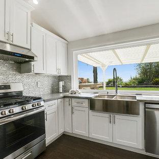 Inredning av ett modernt mellanstort grå grått kök, med en rustik diskho, skåp i shakerstil, vita skåp, bänkskiva i kvarts, grått stänkskydd, glaspanel som stänkskydd, rostfria vitvaror, laminatgolv, en köksö och brunt golv