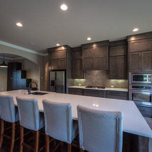 リトルロックの広いトランジショナルスタイルのおしゃれなキッチン (アンダーカウンターシンク、シェーカースタイル扉のキャビネット、中間色木目調キャビネット、珪岩カウンター、ベージュキッチンパネル、レンガのキッチンパネル、シルバーの調理設備、セラミックタイルの床) の写真
