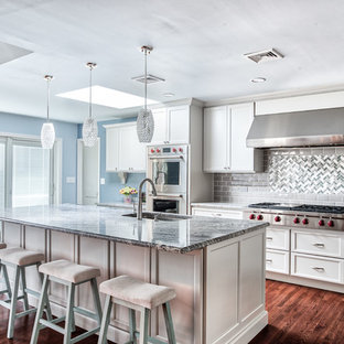Large transitional kitchen pictures - Inspiration for a large transitional l-shaped medium tone wood floor and brown floor kitchen remodel in New York with an undermount sink, granite countertops, gray backsplash, glass tile backsplash, stainless steel appliances, an island, shaker cabinets and white cabinets