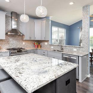 Moderne Küche mit Unterbauwaschbecken, Schrankfronten im Shaker-Stil, weißen Schränken, Granit-Arbeitsplatte, Küchenrückwand in Metallic, Rückwand aus Glasfliesen, Küchengeräten aus Edelstahl, Vinylboden, Kücheninsel, braunem Boden und blauer Arbeitsplatte in Philadelphia