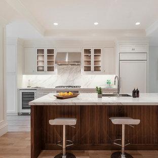 Exemple d'une cuisine américaine avec un évier encastré, un placard avec porte à panneau encastré, des portes de placard blanches, un plan de travail en surface solide, une crédence grise, un électroménager en acier inoxydable, un sol en bois clair, un îlot central, un plan de travail gris et un plafond décaissé.