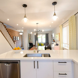 Inspiration for a medium sized contemporary kitchen in Toronto with a submerged sink, flat-panel cabinets, white cabinets, engineered stone countertops, white splashback, metro tiled splashback, stainless steel appliances, medium hardwood flooring, a breakfast bar and brown floors.