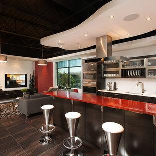 バンクーバーの中くらいのモダンスタイルのおしゃれなキッチン (アンダーカウンターシンク、ガラス扉のキャビネット、ステンレスキャビネット、白いキッチンパネル、パネルと同色の調理設備、ガラスカウンター、セラミックタイルの床、赤いキッチンカウンター) の写真