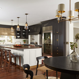 Large elegant l-shaped dark wood floor and brown floor eat-in kitchen photo in Other with beaded inset cabinets, black cabinets, quartzite countertops, white backsplash, subway tile backsplash, stainless steel appliances, an island, an undermount sink and white countertops