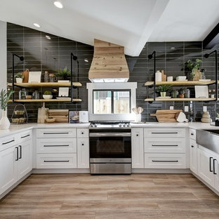 Design ideas for a mid-sized contemporary u-shaped kitchen in Austin with a farmhouse sink, shaker cabinets, white cabinets, black splashback, stainless steel appliances, brown floor and white benchtop.