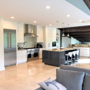 This is an example of a mid-sized contemporary l-shaped eat-in kitchen in Chicago with an undermount sink, white cabinets, white splashback, subway tile splashback, stainless steel appliances, with island, beige floor, multi-coloured benchtop, flat-panel cabinets, granite benchtops and porcelain floors.