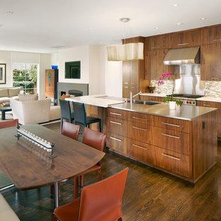 Foto de cocina en L, contemporánea, abierta, con electrodomésticos de acero inoxidable, salpicadero de azulejos en listel, salpicadero beige, puertas de armario de madera oscura, armarios con paneles lisos, fregadero integrado y encimera de cuarcita