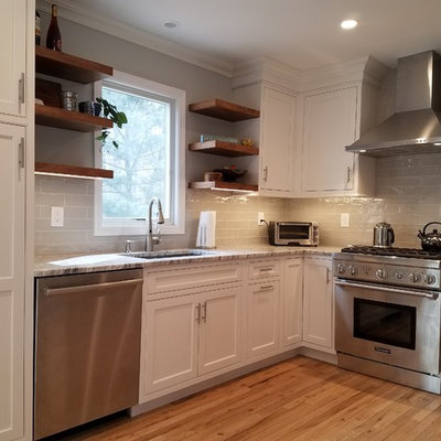 Inspiration for a mid-sized craftsman light wood floor kitchen remodel in New York with an undermount sink, beaded inset cabinets, white cabinets, granite countertops, gray backsplash, porcelain backsplash, stainless steel appliances, an island and multicolored countertops