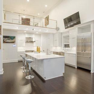 Bild på ett stort funkis kök och matrum, med en rustik diskho, vita skåp, stänkskydd i glaskakel, bambugolv och en köksö