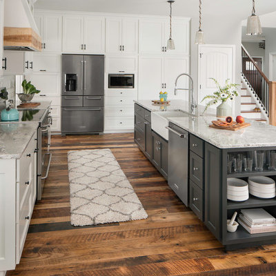 Example of a huge transitional galley medium tone wood floor and brown floor eat-in kitchen design in Columbus with a farmhouse sink, shaker cabinets, white cabinets, quartz countertops, white backsplash, ceramic backsplash, stainless steel appliances and an island