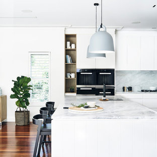 Design ideas for a large scandinavian l-shaped open plan kitchen in Sydney with flat-panel cabinets, white cabinets, marble benchtops, white splashback, stone slab splashback, stainless steel appliances, medium hardwood floors, with island and brown floor.