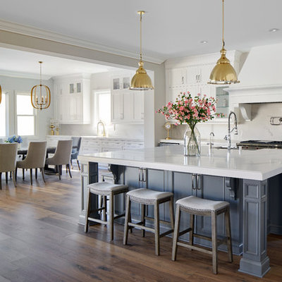 Inspiration for a mid-sized transitional galley medium tone wood floor and multicolored floor eat-in kitchen remodel in Los Angeles with white cabinets, solid surface countertops, white backsplash, marble backsplash, stainless steel appliances, an island, white countertops and recessed-panel cabinets