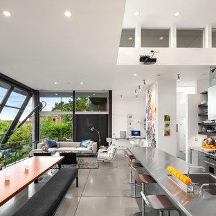 Cette image montre une très grande cuisine ouverte linéaire minimaliste avec un évier intégré, un placard à porte plane, une façade en inox, un plan de travail en inox, une crédence métallisée, une crédence en dalle métallique, un électroménager en acier inoxydable, béton au sol, un îlot central, un sol gris et un plan de travail gris.