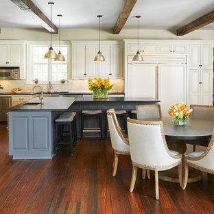 Inspiration för mellanstora klassiska kök, med en undermonterad diskho, luckor med upphöjd panel, vita skåp, vitt stänkskydd, rostfria vitvaror, mellanmörkt trägolv, en köksö, brunt golv och stänkskydd i porslinskakel