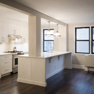 Eat-in kitchen - small modern galley porcelain floor eat-in kitchen idea in New York with an island, white cabinets, white backsplash, stainless steel appliances, an undermount sink, quartzite countertops, glass tile backsplash and shaker cabinets