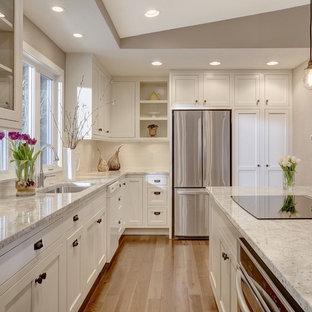 Diseño de cocina en U, clásica renovada, con fregadero bajoencimera, armarios estilo shaker, puertas de armario blancas, electrodomésticos de acero inoxidable y una isla