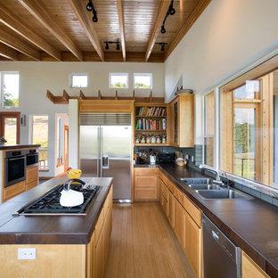 Offene, Zweizeilige, Große Moderne Küche mit Küchengeräten aus Edelstahl, Triple-Waschtisch, hellbraunen Holzschränken, Rückwand aus Keramikfliesen, braunem Holzboden, Kücheninsel, Schrankfronten mit vertiefter Füllung, bunter Rückwand und braunem Boden in Sonstige