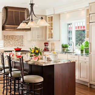 Large traditional l-shaped eat-in kitchen in Boston with an undermount sink, raised-panel cabinets, beige cabinets, granite benchtops, beige splashback, porcelain splashback, panelled appliances, medium hardwood floors and with island.