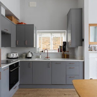 Small arts and crafts l-shaped open plan kitchen in London with an integrated sink, flat-panel cabinets, grey cabinets, solid surface benchtops, white splashback, limestone splashback, stainless steel appliances, laminate floors and no island.