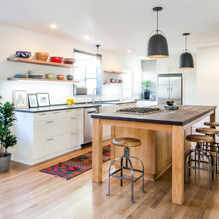 Contemporary kitchen ideas - Trendy u-shaped light wood floor kitchen photo in Santa Barbara with a farmhouse sink, white cabinets, white backsplash, stainless steel appliances, an island and shaker cabinets