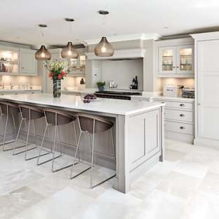 This is an example of a medium sized classic l-shaped kitchen in Manchester with shaker cabinets, grey cabinets, an island, beige floors and white worktops.