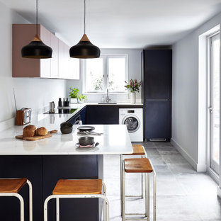 Inspiration for a mid-sized scandinavian u-shaped kitchen in London with flat-panel cabinets, solid surface benchtops, ceramic floors, a peninsula, grey floor, white benchtop, an undermount sink and black cabinets.