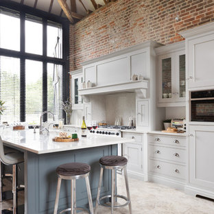 This is an example of a large traditional l-shaped open plan kitchen in Essex with a built-in sink, shaker cabinets, grey cabinets, quartz worktops, white splashback, stainless steel appliances, limestone flooring, an island, beige floors and white worktops.