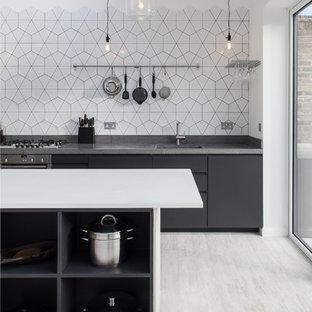 ロンドンのコンテンポラリースタイルのおしゃれなアイランドキッチン (アンダーカウンターシンク、フラットパネル扉のキャビネット、黒いキャビネット、白いキッチンパネル) の写真